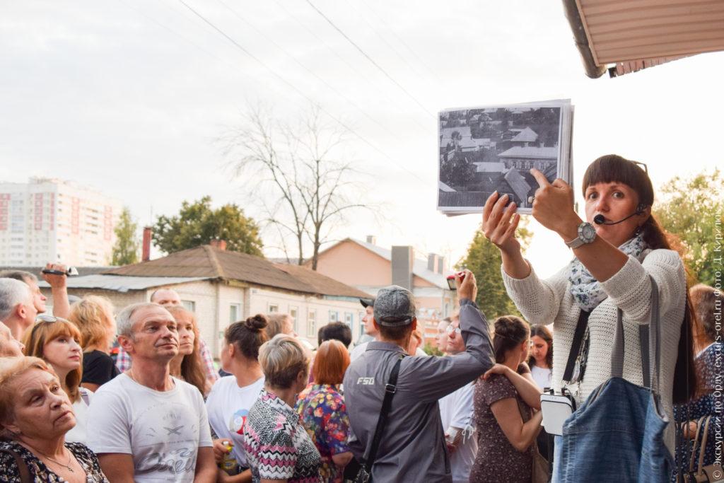 Экскурсовод показывает старое фото дома на фоне него самого.