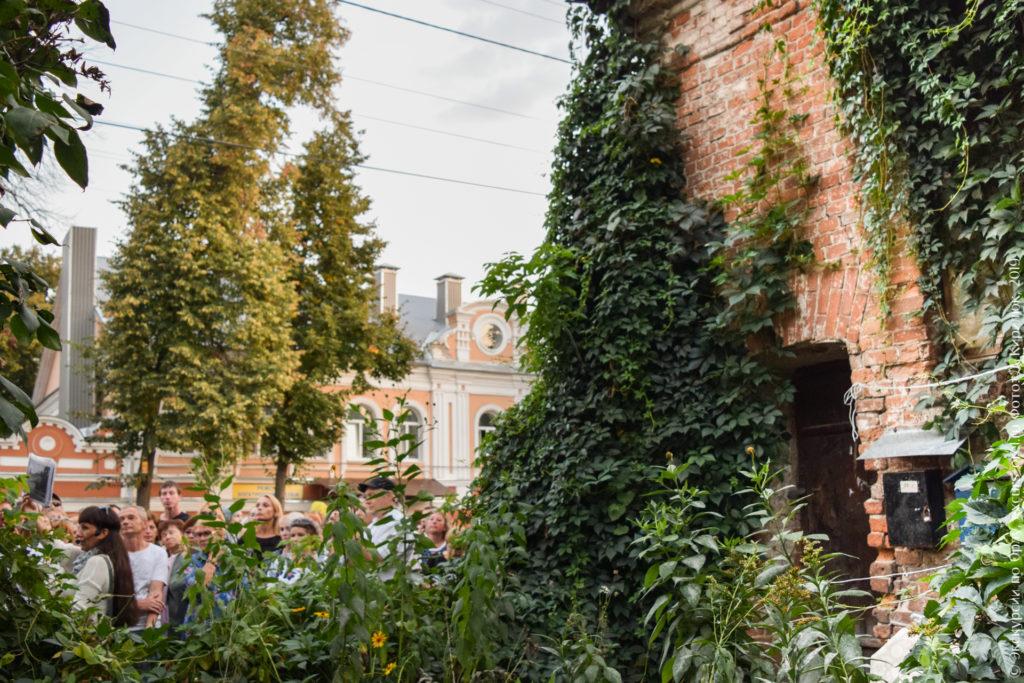 Краснокирпичная боковая стена дома, наполовину закрытая густым зеленым вьюном.