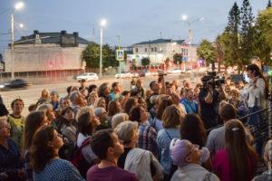 Экскурсанты, не менее 50 человек, на фоне перекрестка с активным автомобильным движением, вечер. На той стороне дом за банером.