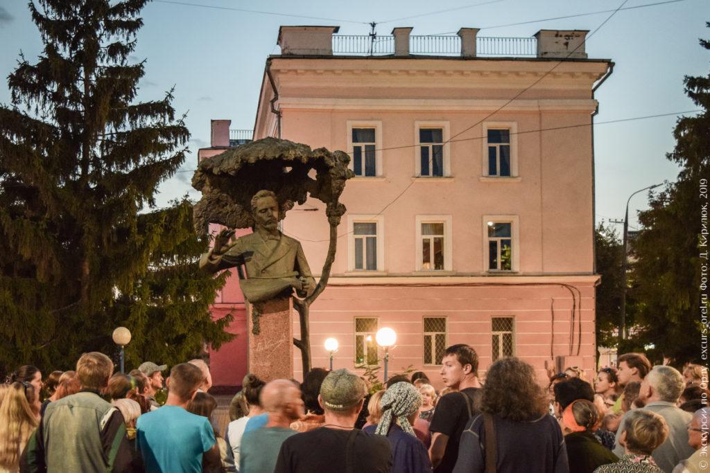 Люди перед памятником Калинникову на фоне трехэтажного здания.