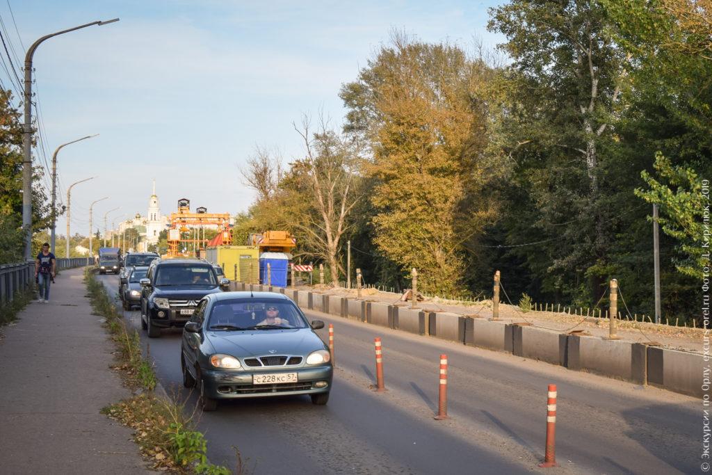 Перекрытый наполовину мост, половина перил снята, полотно вскрыто, на заднем плане видна большая оранжевая установка (мостовой кран). Справа от моста - высокие деревья. По открытой части моста едут машины.