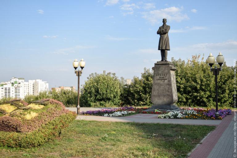 Памятник Бунину на высоком постаменте на фоне обрыва. Перед памятником топиарная книга.