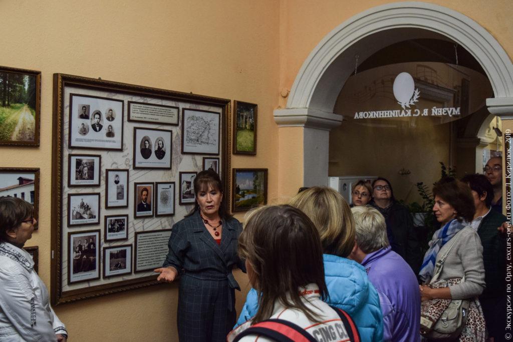 Экскурсанты в музее слушают экскурсовода, на стенах - фото, карта, цитаты.