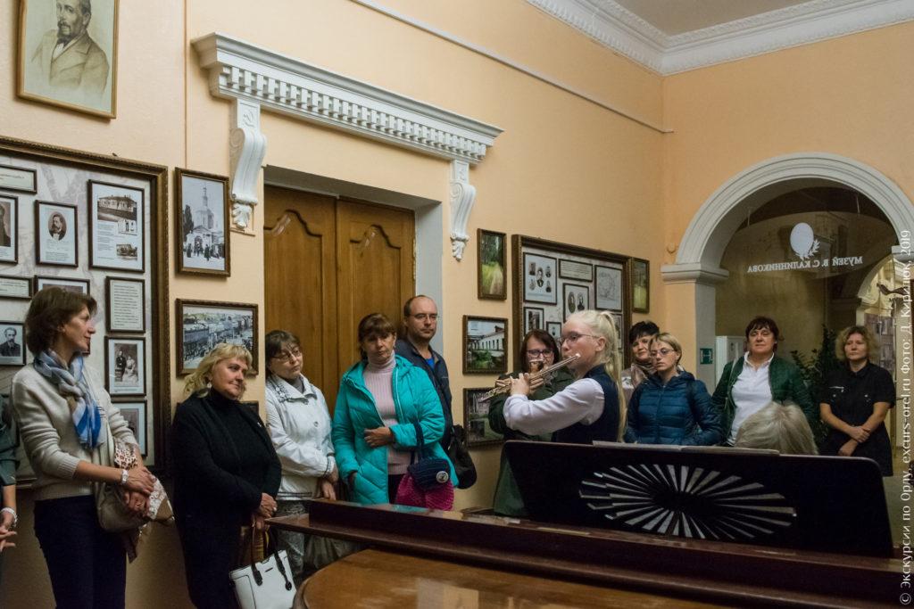 Девочка в музее Калинникова играет на флейте, ей аккомпанируют на рояле.