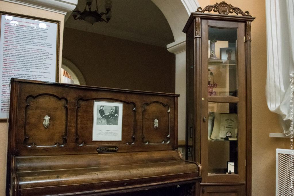 Пианино и высокий шкаф с нотами, часами и т.д.