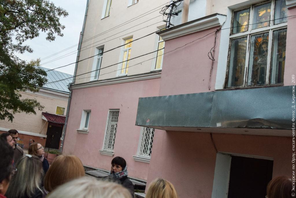 Розовое 3-этажное здание, над чёрным ходом цветной витраж.