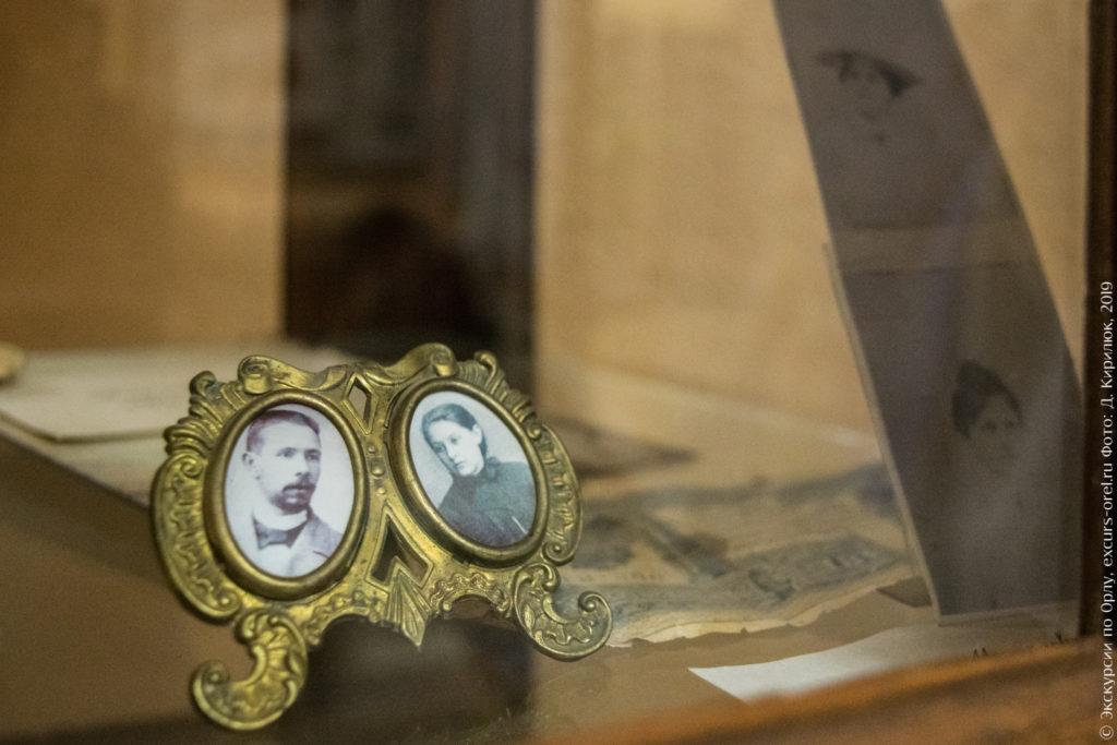 Маленькая рамка из жёлтого металла под два фото, на них мужской и женский портреты.