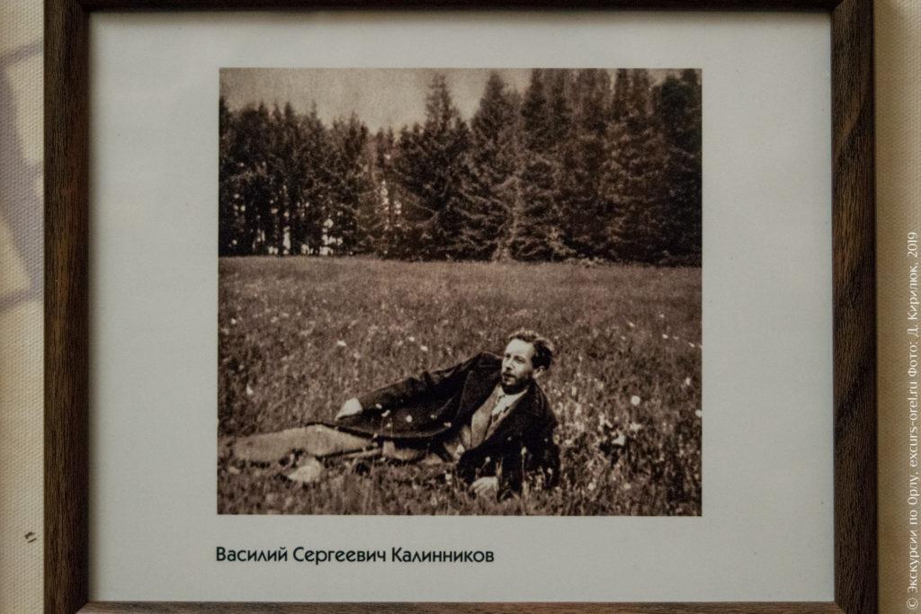 Старое фото, мужчина в пиджаке лежит на опушке леса.
