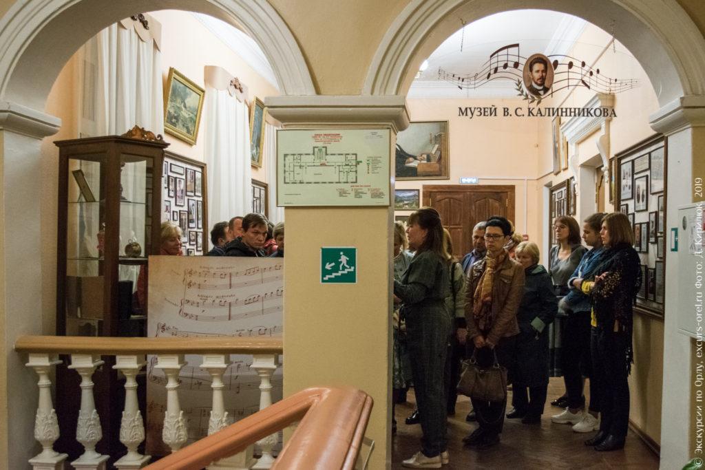 """Просторное помещение с картинами и стендами, под входной аркой надпись на стекле """"Музей В.С. Калинникова""""."""