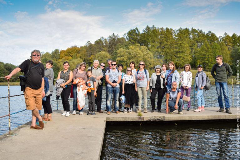 Экскурсанты на фоне пруда и леса.