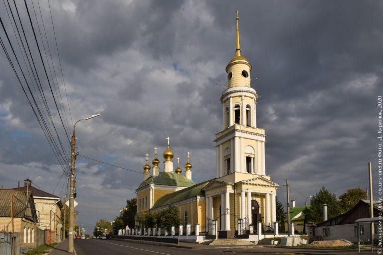 Бело-желтая церковь с зеленой крышей и золотыми главками. С высокой колокольней с портиком и шпилем.