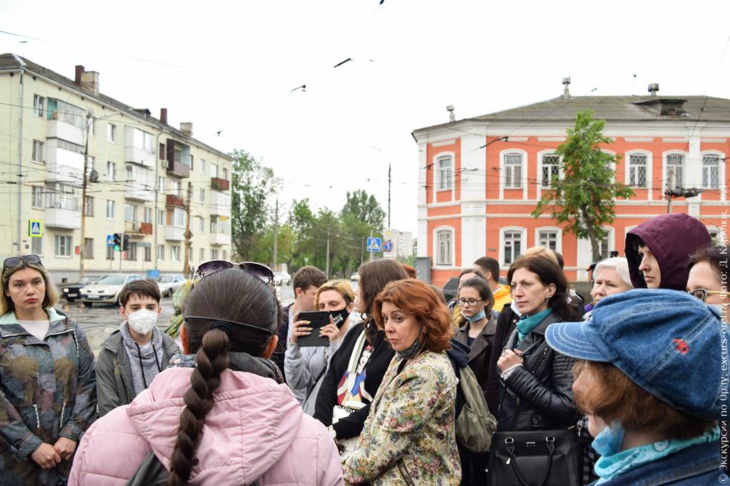 Экскурсанты на фоне дореволюционного городского особняка.