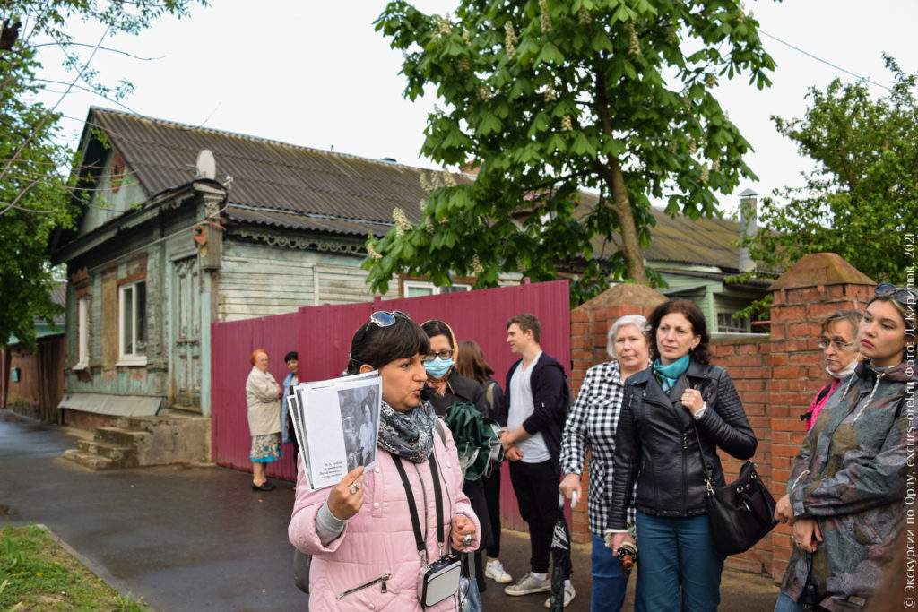 Экскурсанты на фоне одноэтажного деревянного дома с остатками аутентичной резьбы.