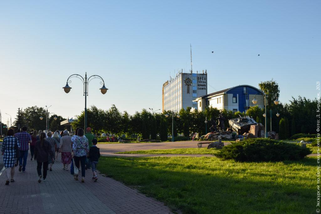 Сквер, за ним высокое промышленное здание с орденом на боковом фасаде.