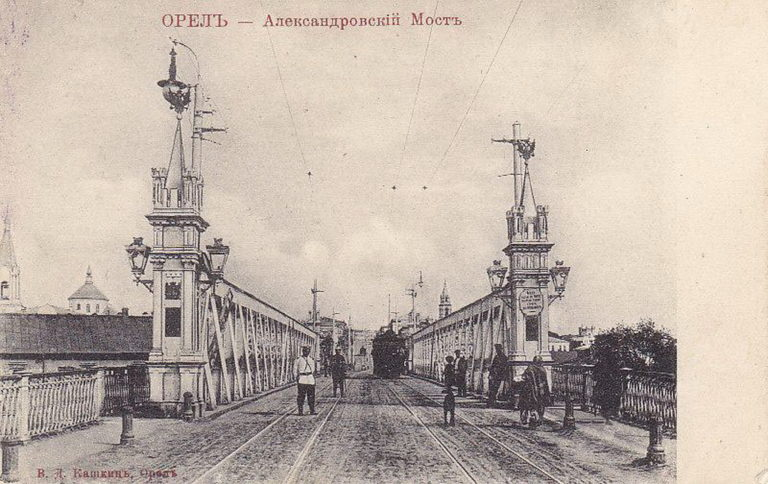 Старая открытка с изображением металлического моста с башенками, по мосту едет трамвай.