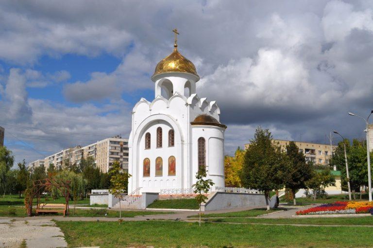 Белый однокупольный храм на фоне микрорайона.