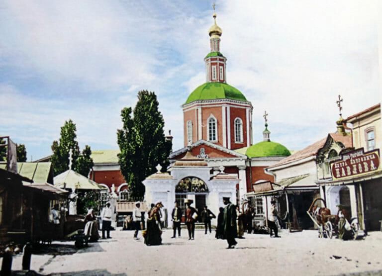 Цветная дореволюционная карточка с изображением церкви с красными стенами, белой отделкой и зелеными куполами.