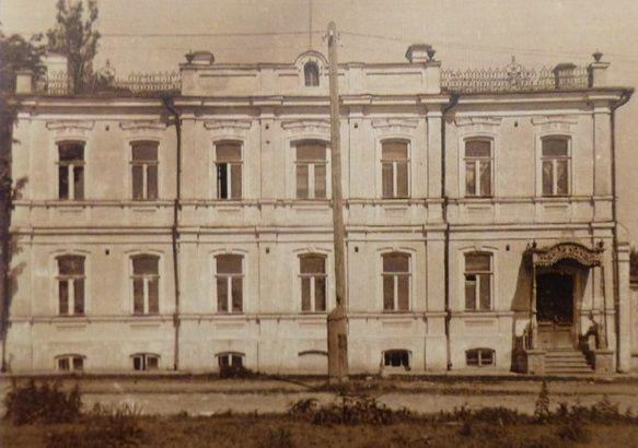Старое фото каменного двухэтажного дома с чугунным крыльцом сбоку.
