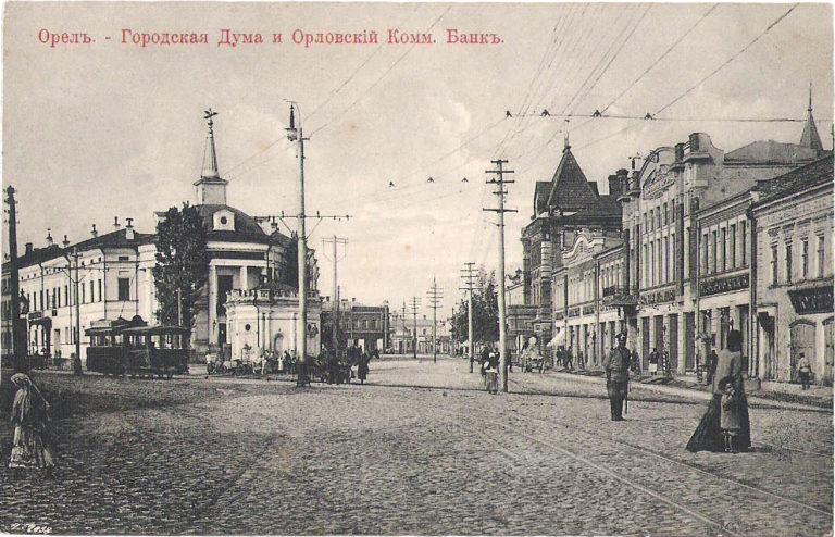 Старая открытка с улицей, застроенной разными по стилю зданиями.