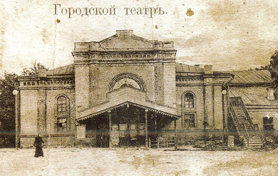 """Старая открытка с фото одноэтажного каменного здания с высокими окнами и широким крыльцом с деревянной двускатной крышей, надпись на открытке """"Городской театръ""""."""