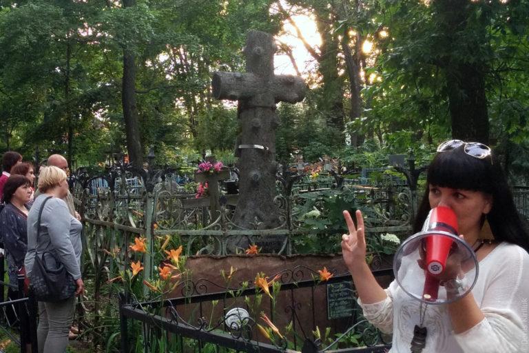 Экскурсовод на фоне надбгробия в виде креста с обрубленными суками.