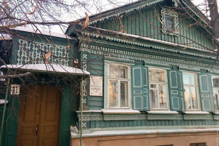 Деревянный дом с резьбой, наличниками. мемориальной доской.