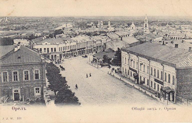 Старая открытка с видом города выше уровня крыш. Двухэтажные дома, церкви с колокольнями, мосты над рекой.
