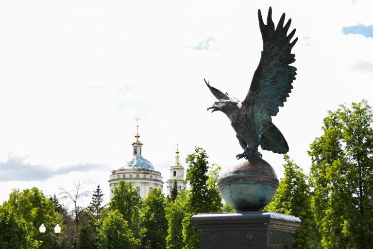 Скульптура орел на шаре на фоне церкви