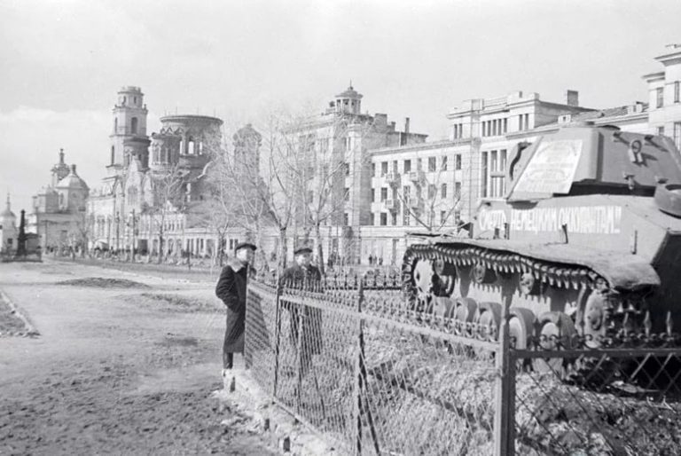 Танк на земляном холме на фоне частично разрушенных церквей и зданий.