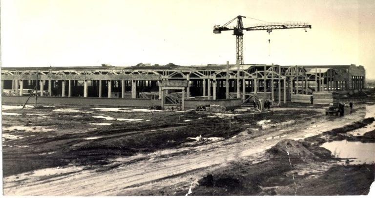 Старое фото строительства заводских корпусов среди луж и грязи.
