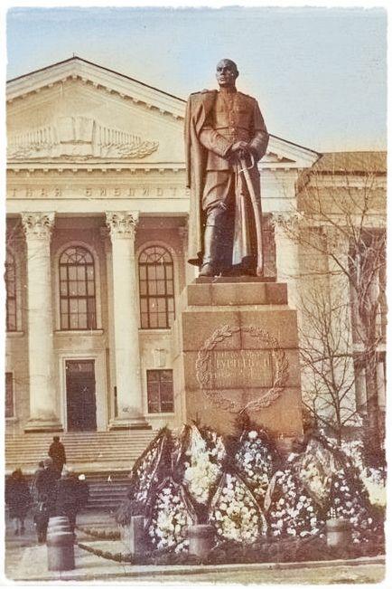 Памятник генералу перед зданием библиотеки с колоннами.