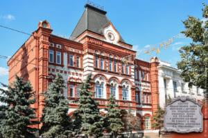 Красно-белое здание в русском стиле и зеленые ели перед ним.