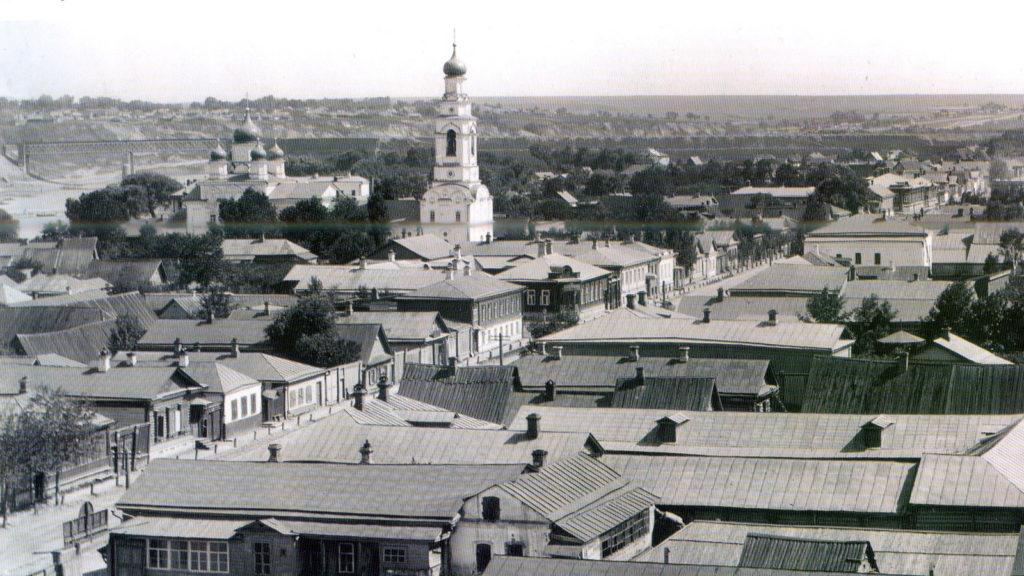 Старое фото, общий вид города с точки выше крыш. Слева видны река и железнодорожный мост, потом - церковь с высокой колокольней.