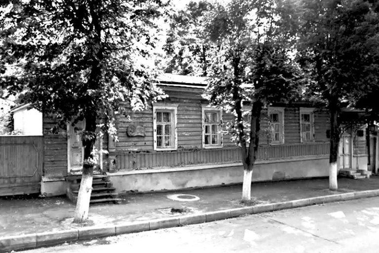 Деревянный дом с мемориальной доской, частично закрыт деревьями, растущими из тротуара.