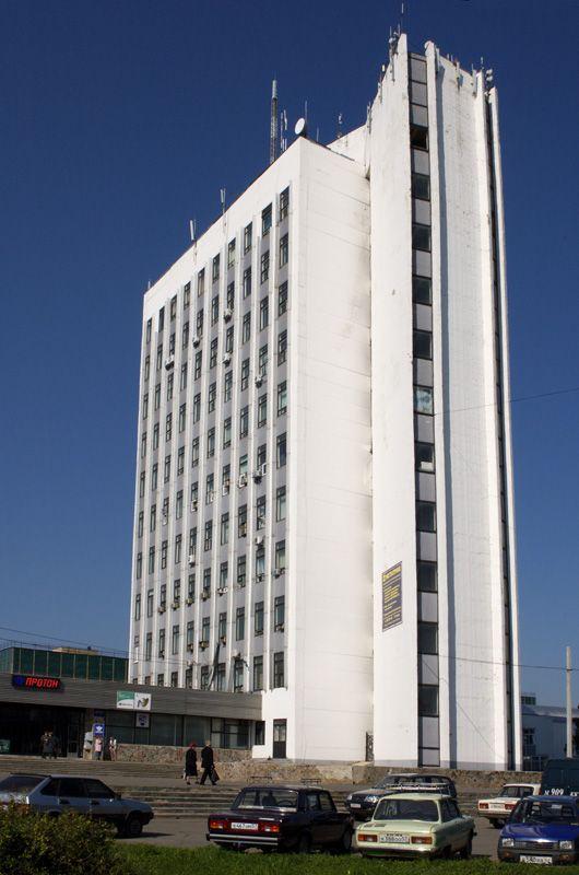 Высокое белое здание. Проходная со светодиодным таблом.