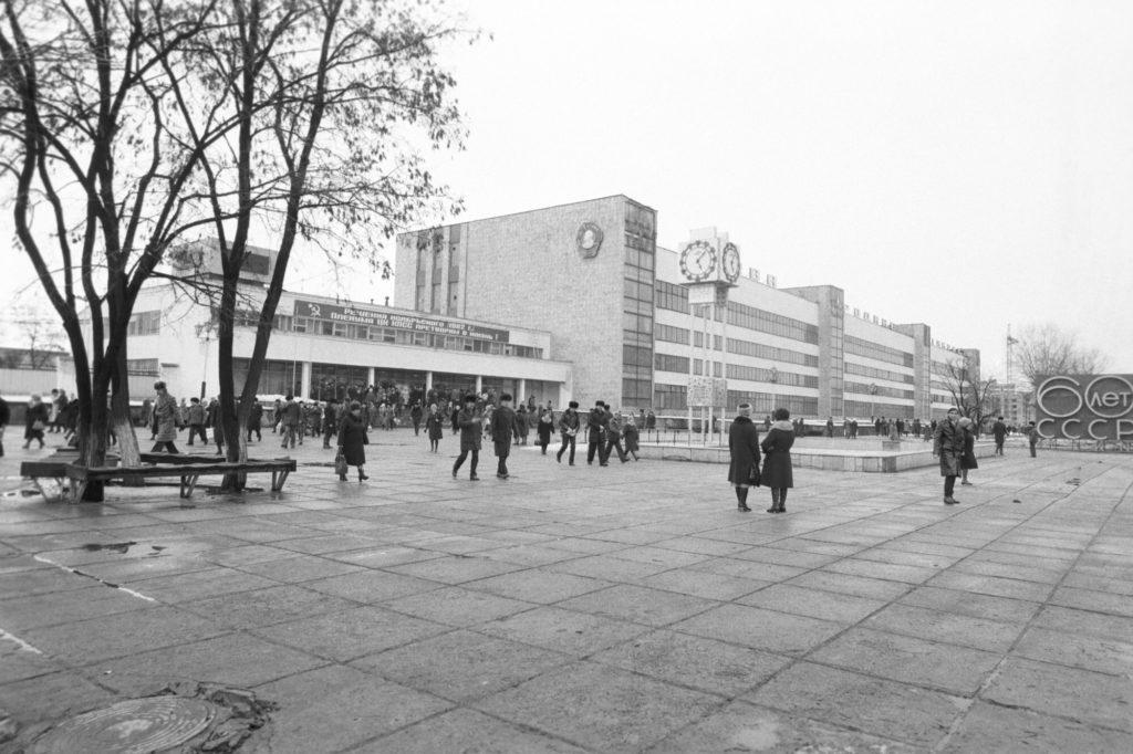 Старое фото советского завода с часами и фонтаном перед проходной. Много людей.